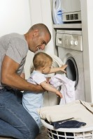 photo of man teaching his son to do laundry